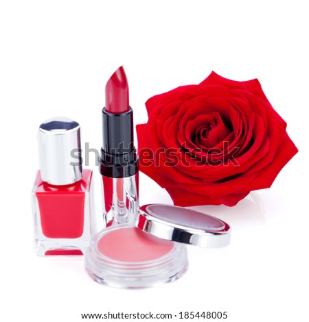 Display of fashionable cosmetics in their containers including a compact of powder or blusher, nail varnish and lipstick with a natural fresh red rose