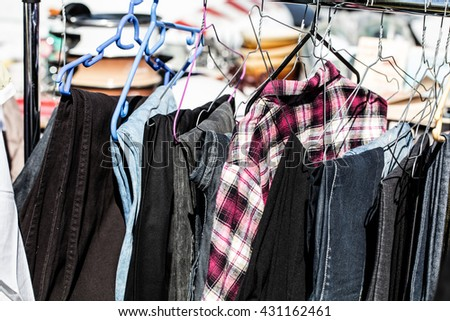 display of male second hand clothes on rack for charity,donation,reusing or reselling for second life sold at flea market for fashion fans or economic shopping - stock photo