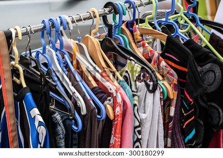 display of second hand clothes on rack for charity,donation,reusing or reselling for second life sold at garage sale for fashion fans or economic shopping - stock photo