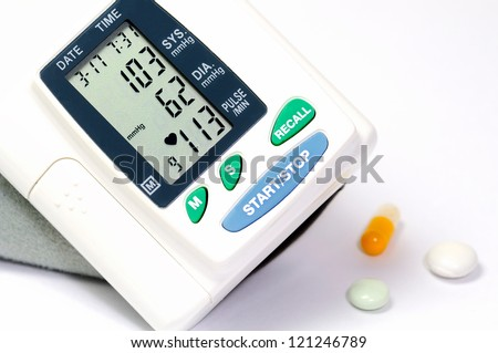Display on a sphygmomanometer indicates low blood  pressure. Near by lying tablets.