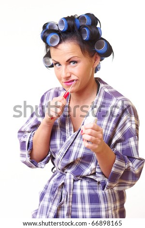 Displease housewife in bathrobe with tooth brush and curlers - stock photo