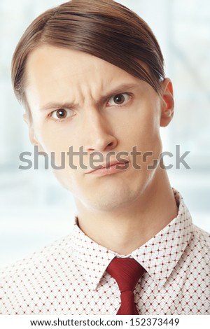 Displeased businessman at his office. Vertical portrait - stock photo