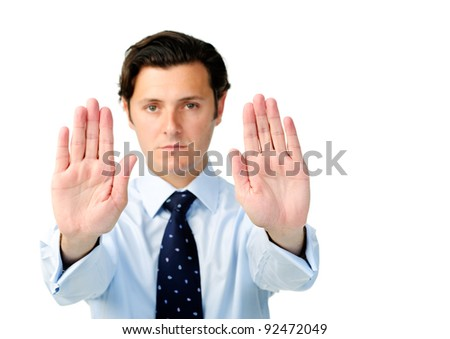 Displeased businessman holds both hands up to show a stop signal