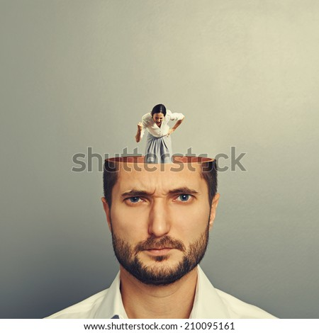 displeased man listening small angry screaming woman in his head. photo over grey background - stock photo
