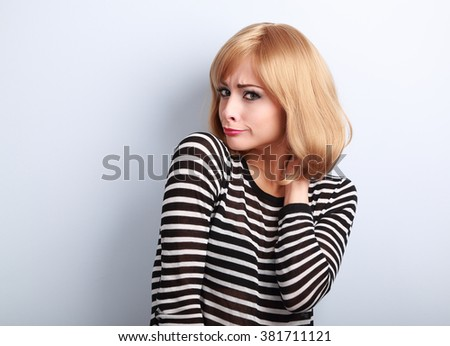 Displeased suspicious blond woman looking skeptical on blue background - stock photo