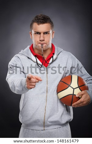 Displeased trainer. Portrait of angry young coach whistling and scolding. Studio shot on black background - stock photo