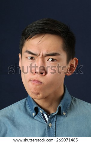 Displeased young Asian man making face and looking at camera - stock photo