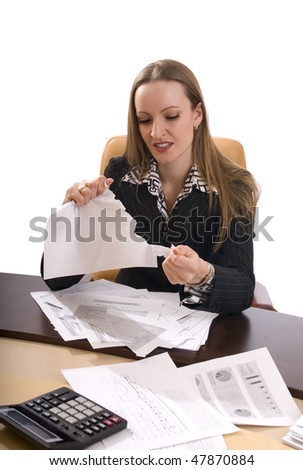 Displeased young business woman tearing documents angrily on her desk