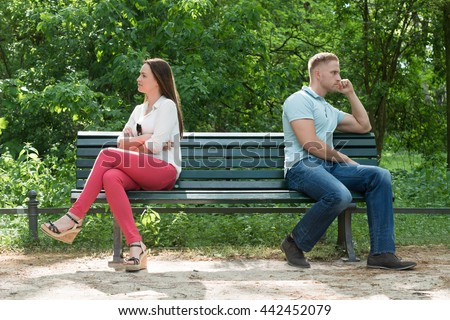 Displeased Young Couple Sitting On Bench In Park - stock photo