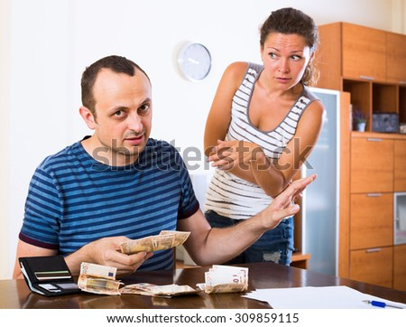 Displeased young woman and her husband counting money for paying debts