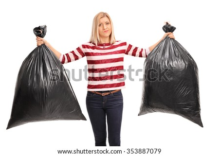 Displeased young woman holding two black trash bags and looking at the camera isolated on white background - stock photo