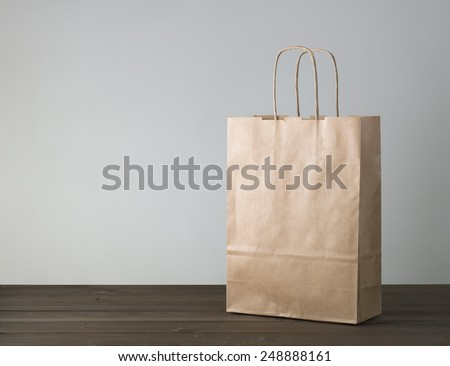 disposable bag of kraft paper on a wooden table - stock photo