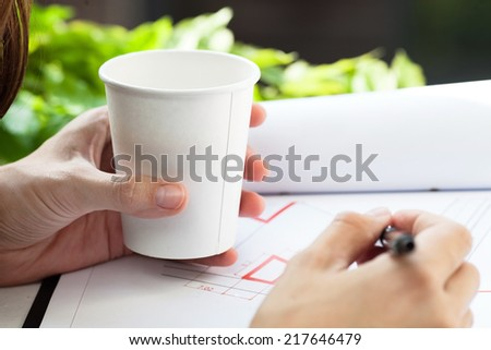 Disposable coffee cup in hand. - stock photo