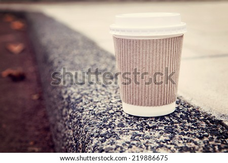Disposable coffee cup on sidewalk with city in background. - stock photo