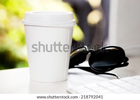 Disposable coffee cup on table near computer keyboard - stock photo