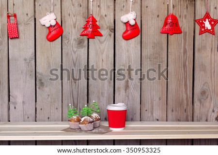 Disposable paper coffee cup with three tasty muffins decorated for Christmas Holidays and ready to takeaway.Winter cozy cafeteria background - stock photo