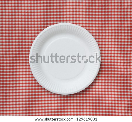 Disposable paper plate on a checkered cloth. - stock photo