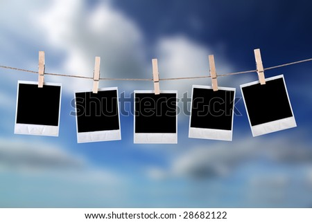 disposable photo frames hanging in the rope with blue sky - stock photo