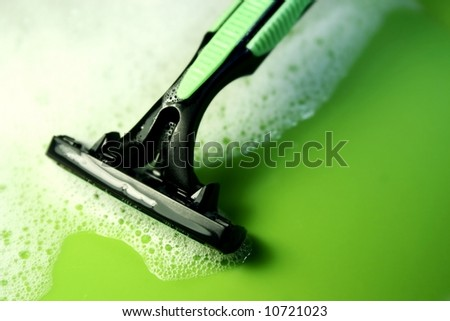disposable razor against a green background - stock photo