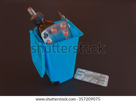 dispose of expired drugs into trash bin - stock photo