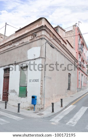 Disrepair Old Vintage Ruined Dirty Home For Sale (Se Vende) with pedestrian crosswalk in Urban Residential Neighborhood in Spain Europe