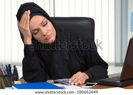 Dissapointed arabic woman, traditional dressed, working at desk, inside her office.