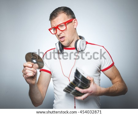 Dissapointed dj looking to cd. Unhappy party guy. Studio shot - stock photo