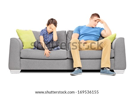 Dissappointed brothers sitting on a sofa isolated on white background - stock photo