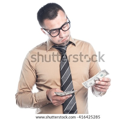 Dissatisfied businessman count - holding money, isolated on white background. Employee young man with small profit. Bankruptcy concept, finacial crisis. - stock photo