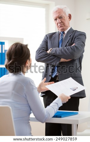 Dissatisfied elderly employer and young female candidate - stock photo