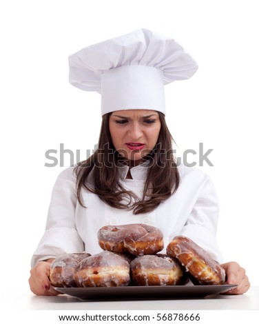 dissatisfied or angry female chef in white uniform and hat with doughnuts