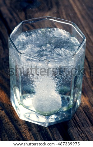 Dissolving Aspirin fizzy pill  in glass of water on wooden background