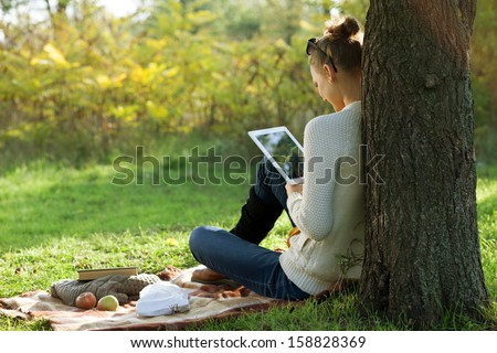 Distance education. Sitting woman using tablet during stroll outdoors - stock photo