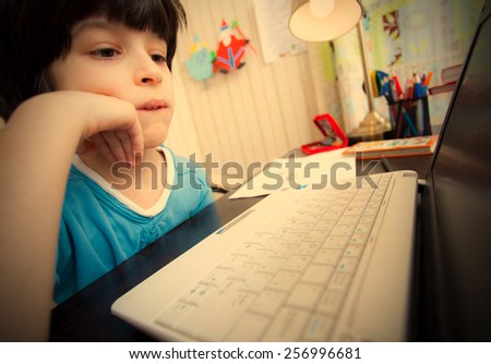 distance learning, a boy with computer in the interior. instagram image retro style - stock photo