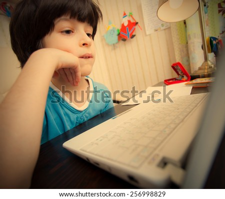distance learning, a child with computer in the interior. instagram image retro style - stock photo