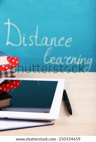 Distance learning concept with tablet and books on blackboard background - stock photo