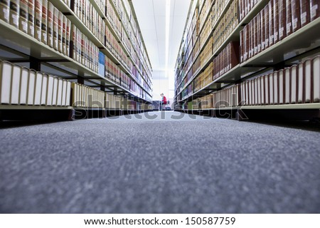 Distance shot of a female in university library with shelves of books in foreground - stock photo