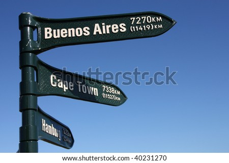 Distance signs, showing directions to Buenos Aires, Cape Town and Hamburg. - stock photo