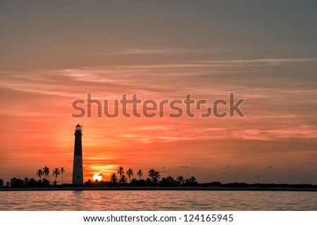 Distance view of Dry Tortugas lighthouse at dramatic sunset - stock photo