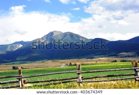 Distant Absaroka Mountains serve as backdrop for this farm surrounded by rustic wooden fence.  Water irrigation system works across field. - stock photo