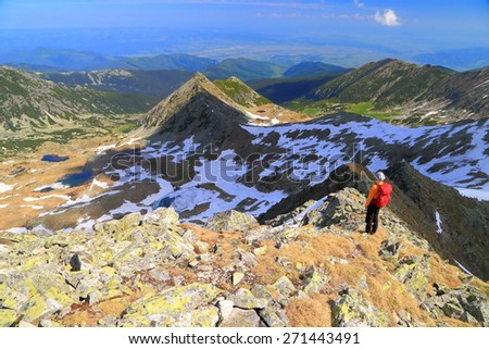 Distant backpacker woman on sunny mountain ridge in summer - stock photo