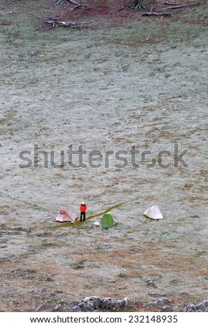 Distant campsite with isolated hiker standing near the tents in cold weather - stock photo