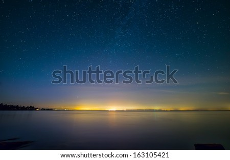 Distant city lights over water with stars - stock photo