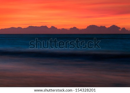 Distant clouds are silhouetted on the horizon with a dramatic sunrise sky over the Atlantic Ocean. - stock photo