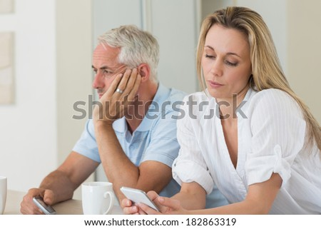 Distant couple sitting at the counter texting at home in the kitchen - stock photo