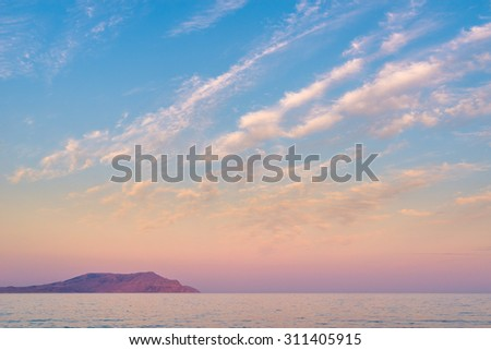 Distant island under beautiful range of clouds formed as parallel lines