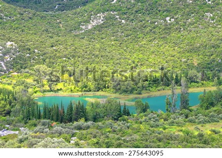 Distant lake surrounded by green hills covered with vegetation near Neretva delta, Croatia - stock photo