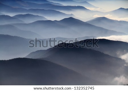 Distant mountain range and thin layer of clouds on the valleys, Romania - stock photo
