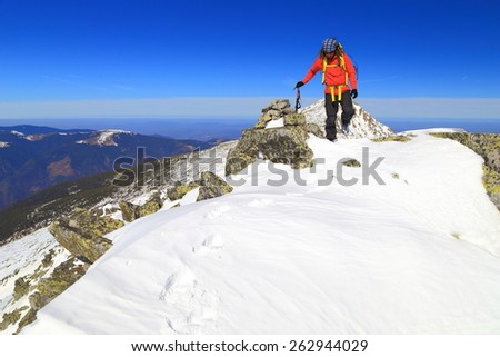 Distant mountaineer on snow covered summit in sunny winter day - stock photo
