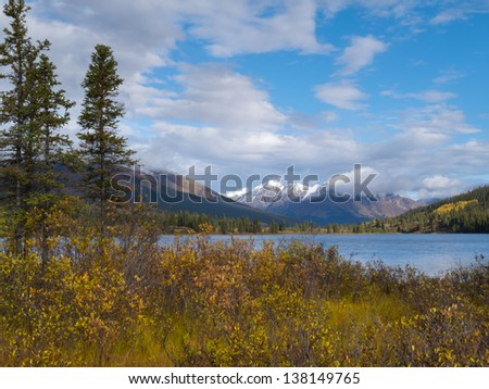 Distant mountains and fall colored willows at the shore of beautiful scenic Lapie Lake  Yukon Territory  Canada - stock photo